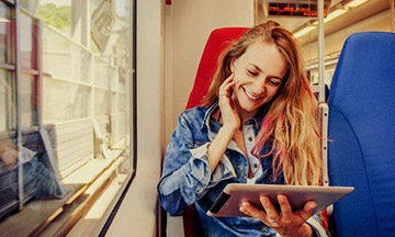 girl-on-train-with-tablet-smiling