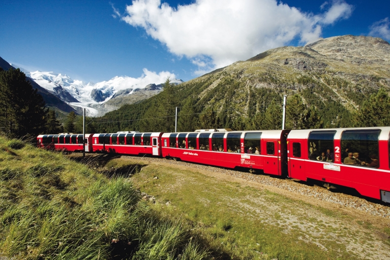 A red train surrounded by green and white mountains