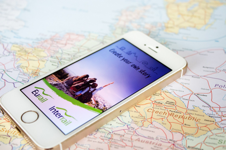 Image of a mobile phone on a map of Europe. The Interrail Rail Planner App is showing on the screen of the phone.