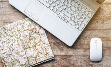 travel-planning-map-laptop-on-tabl